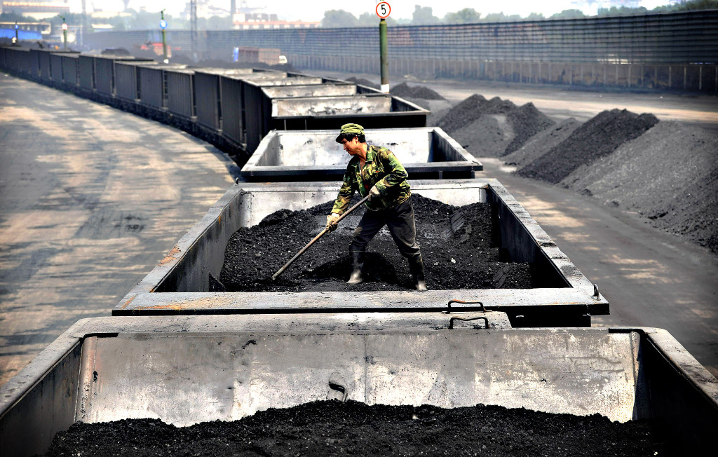 A worker levels the coal on a freight train in Taiyuan in northe