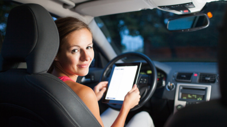 Pretty, female driver using her tablet computer (shallow DOF; co
